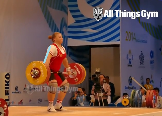 155kg snatch by Tatiana Kashirina. She is over the bar, and her torso is not vertical at hip height.