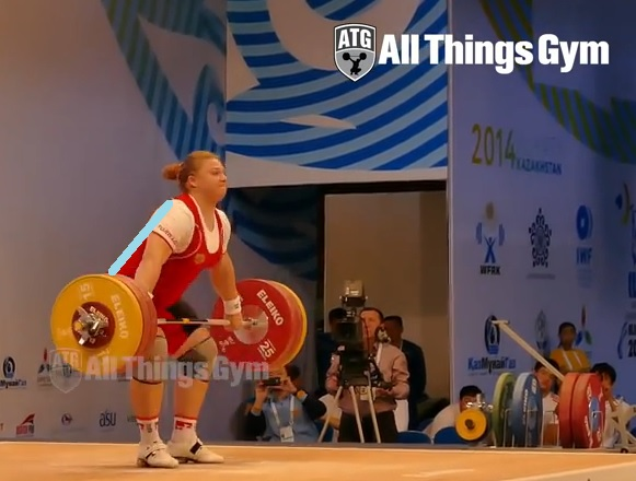 Tatiana Kashirina snatching 155kg. From below the knees to above the knees, the knees have not moved forward. Instead of rebending them actively, she extends them! This makes the biggest difference in bar trajectory and speed under the bar. Notice how she is over the bar - not behind like the active DKB camp teach. Credit All things gym